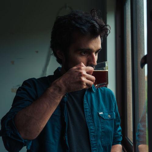 Man drinking tea while looking through window
