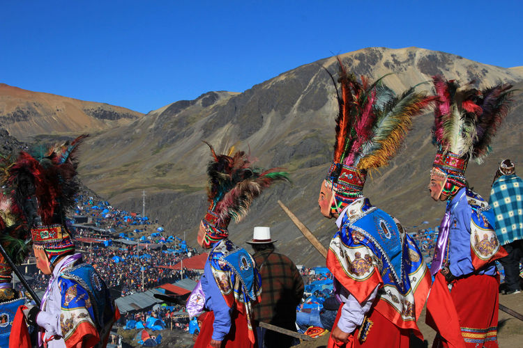 People in traditional clothing dancing on sand against mountains and sky