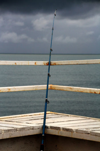 Fishing rod on a dock in a stormy weather Fishing Rod Stormy Weather Dock Fishing Sea Stromy Sky Water