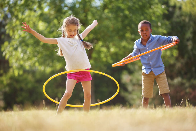 Siblings Playing With Hoops On Field