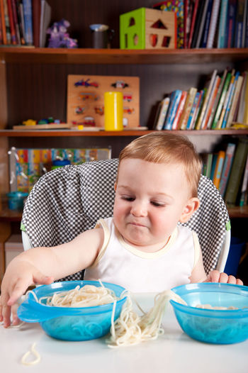 Cute baby boy with food on table at home