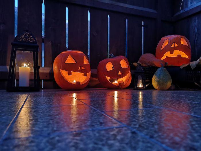View of illuminated pumpkin on wooden floor during halloween