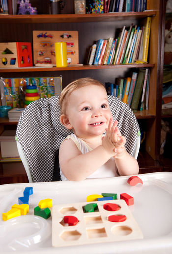 Cheerful baby boy with toys on table sitting at home