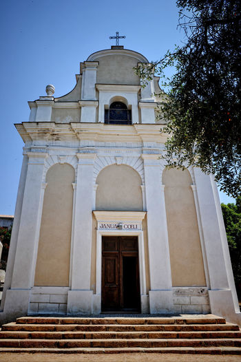 Architecture Cargèse, Catholic Church Corse Cross Janua Coeli Belief Built Structure Catholic Church Corsica Door Entrance Façade Frontón History Low Angle View Outdoors Religion Roman Sky Spirituality Tree