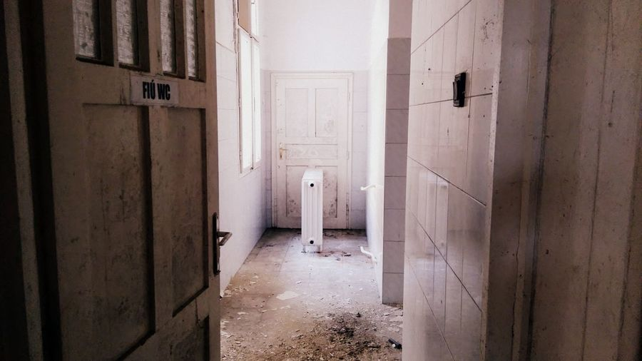 Open door of abandoned public restroom