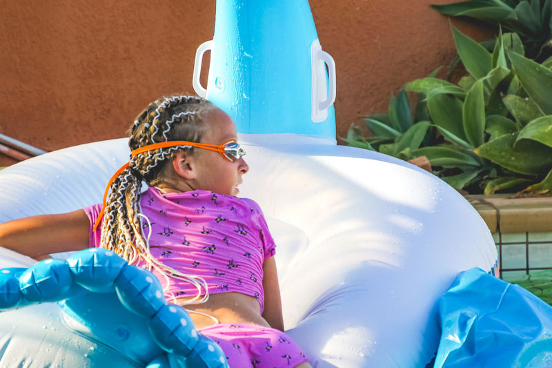 young girl with long hair, wearing a pink swimsuit and swimming goggles, resting against an inflatable in a pool Child Childhood Real People Lifestyles Females Women Girls Leisure Activity Day People Blue Three Quarter Length Innocence Nature Swimming Pool Long Hair Inflatable  Summertime