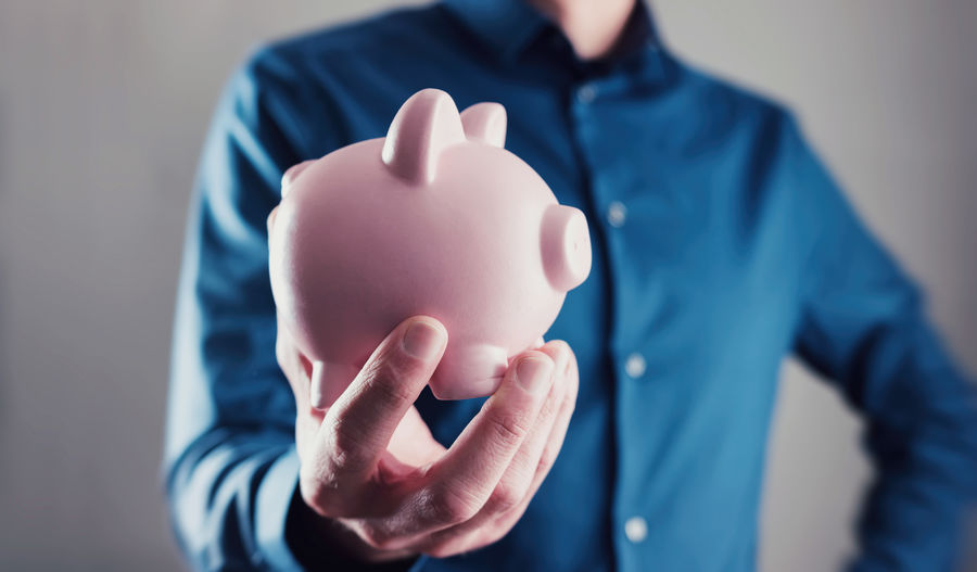 Midsection Of Businessman Holding Pink Piggy Bank