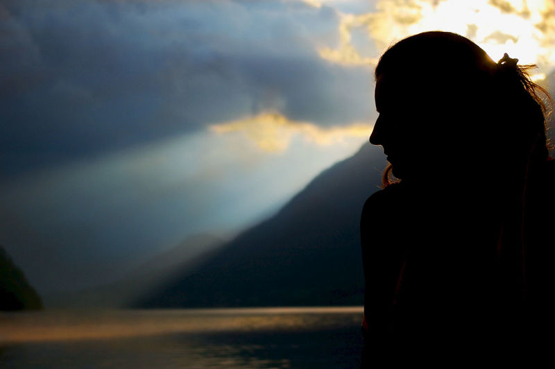 Silhouette Woman Against Mountains And Sky During Sunset
