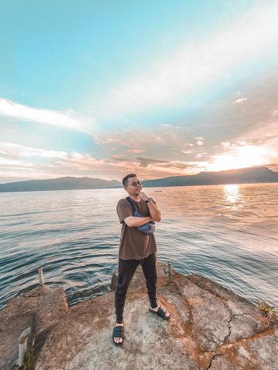 Full length of man standing on rock against sea
