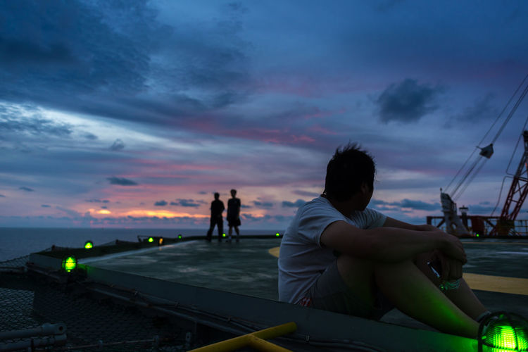 Man sitting on boat moored at sea against sky during sunset