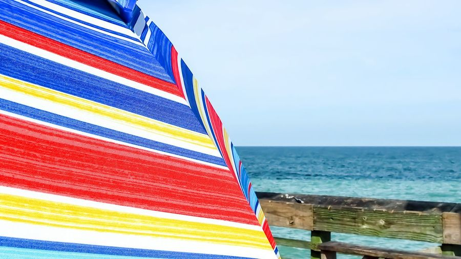 bright colors of an umbrella along the ocean Bradley Olson Bradleywarren Photography Room For Copy Copy Space Copyspace Backgrounds Room For Text Background Water Sea Multi Colored Beach Summer Blue Red Sky Horizon Over Water Close-up Beach Umbrella Parasol Canopy Coast Shore Sunshade Wave Seascape Sun Lounger Coastline Ocean Lounge Chair