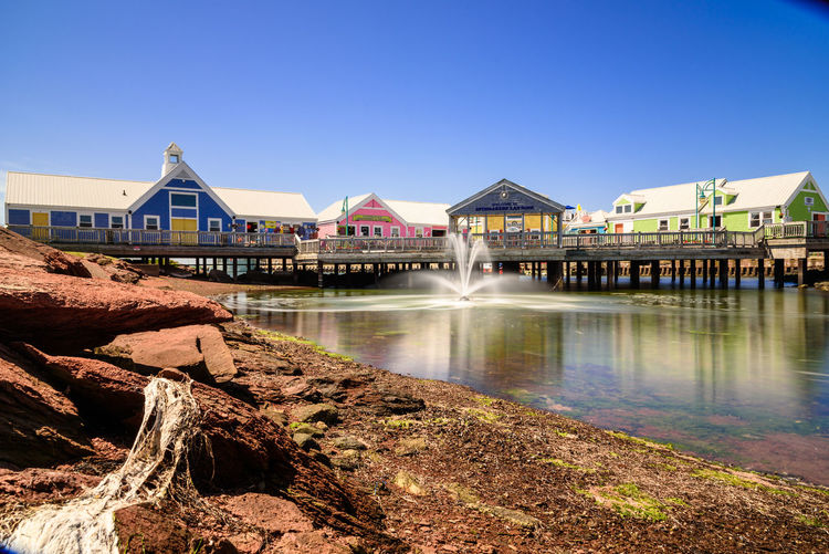 Spinnakers Landing, Prince Edward Island, Canada. Elevated Houses Spinnakers Landing Summerside Water Reflections Architecture Beauty In Nature Blue Sky Building Exterior Built Structure Canada Clear Sky Day Elevated Walkway Long Exposure Multi Color Multi Colours Nature Outdoors Pei Prince Edward Island Scenics Sky Water Water Fountain Waterfront