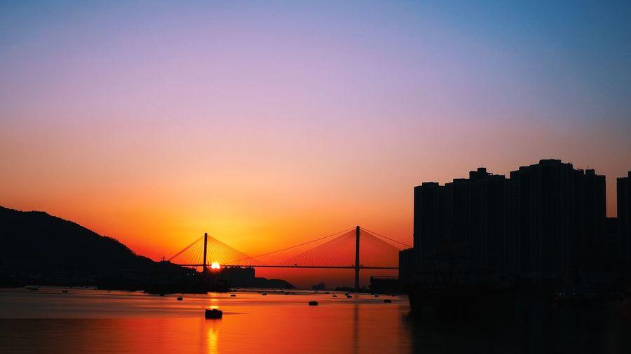 Silhouette bridge over bay against sky during sunset