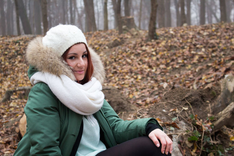 Portrait of woman sitting in forest during winter