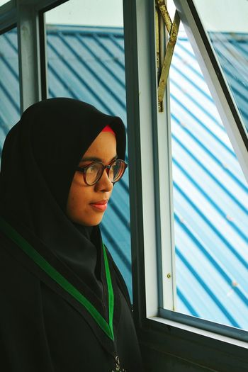 Mid Adult Woman In Hijab Looking Through Window While Standing At Home