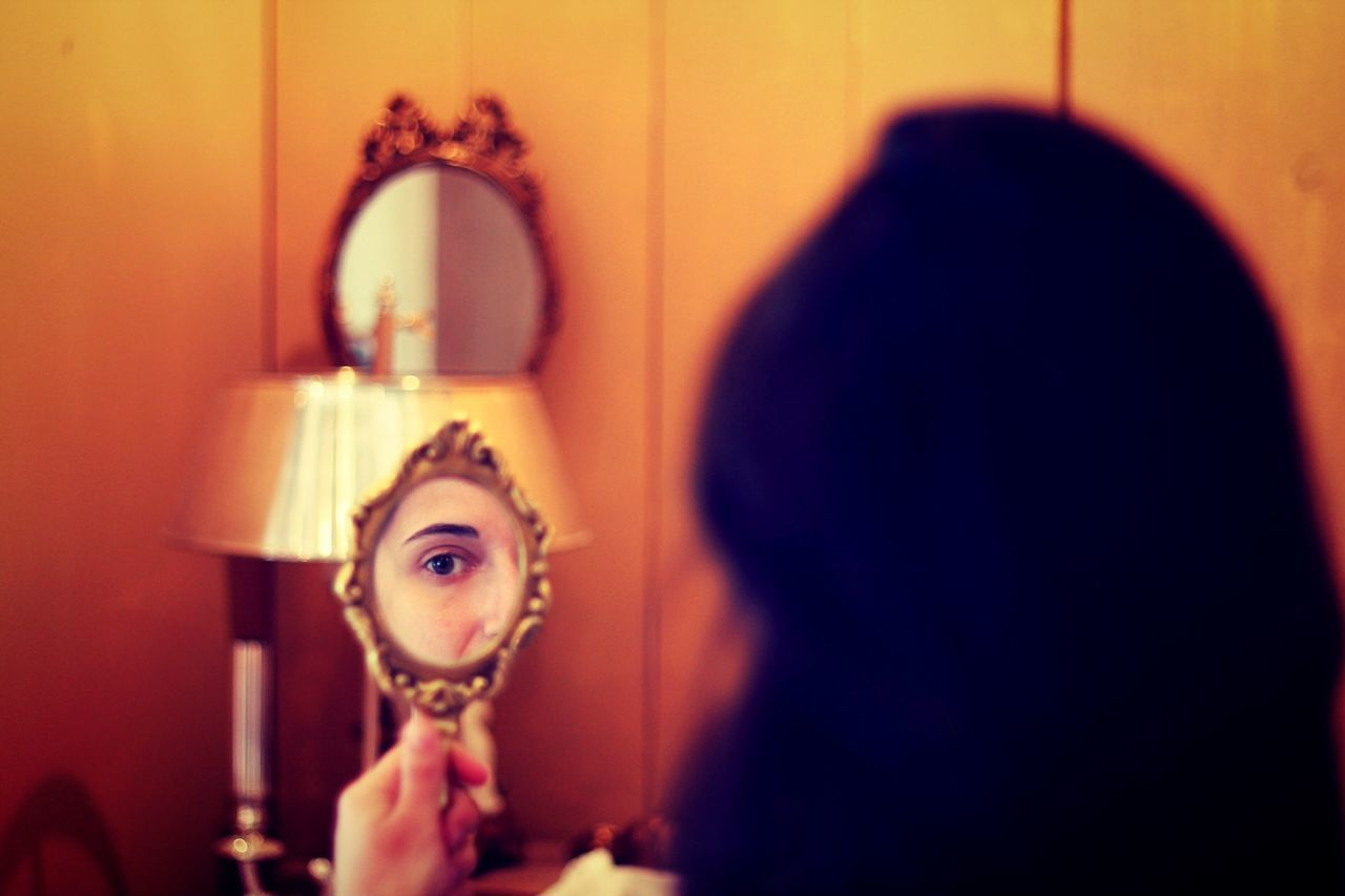 Close-up of a beautiful young woman looking at mirror