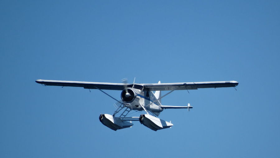 Low angle view of seaplane flying against clear sky