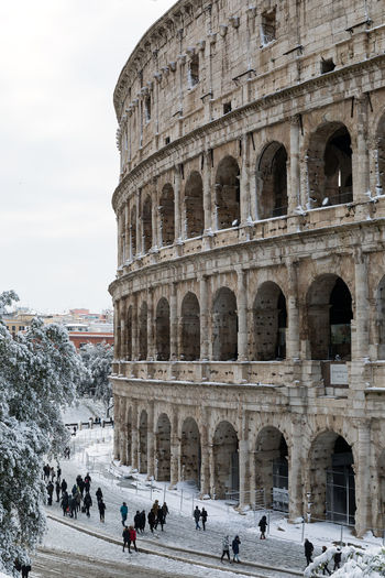 Rome, Italy - February 26, 2018: An exceptional weather event causes a cold and cold air across Europe, including Italy. Snow comes in the capital, covering streets and monuments of a white white coat. In the photo, the Colosseum covered by snow. Buran Winter Amphitheater Ancient Ancient Civilization Arch Archaeology Architecture Building Exterior Built Structure Climate Climate Change Day History Large Group Of People Lifestyles Monument Old Ruin Outdoors Real People Snow Tourism Tourist Travel Travel Destinations
