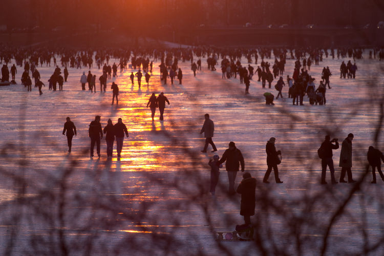 Group of silhouette people in snow during sunset