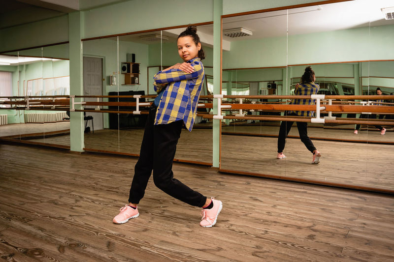 Full length of young black woman dancing alone in choreography hall with mirrors
