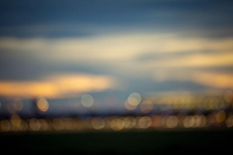 Defocused image of illuminated sea against sky at night