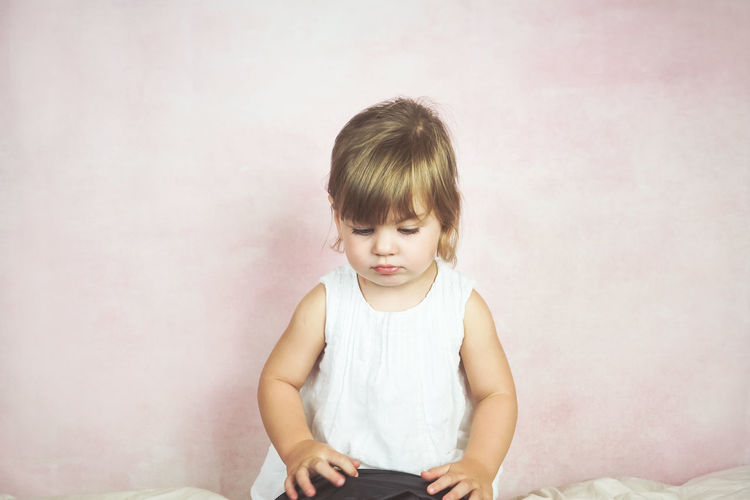 Childhood Child Front View One Person Indoors  Looking Innocence Sitting Three Quarter Length Looking Down Casual Clothing Technology Hair Holding Girls Wireless Technology Studio Shot Offspring Bangs Hairstyle Sad Tired Lonely