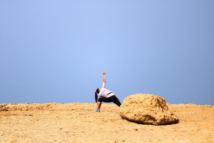 Woman exercising on land against clear sky