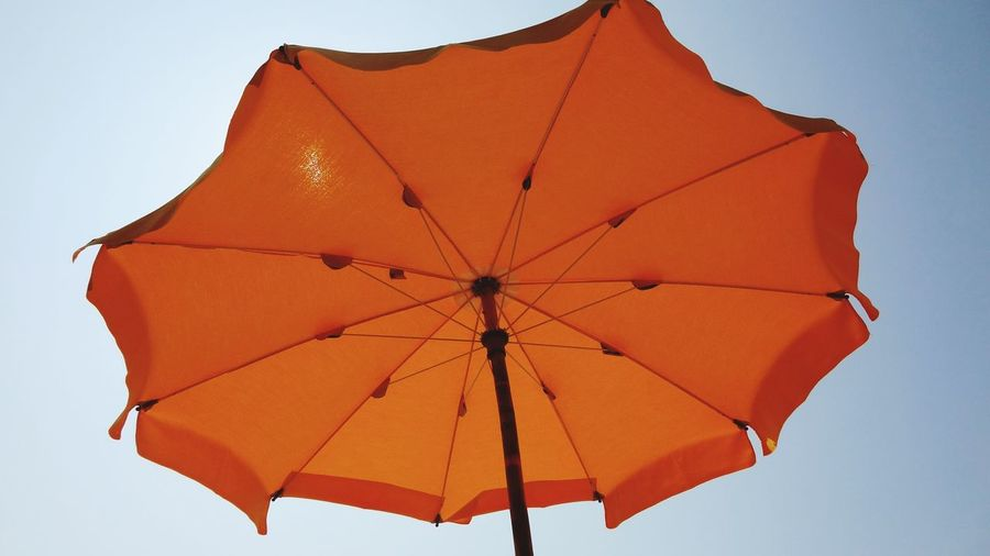 Low Angle View Of Orange Umbrella Against Clear Sky