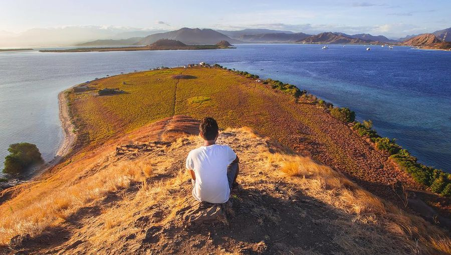 Rear View Of Man Sitting On Cliff Over Sea Against Sky