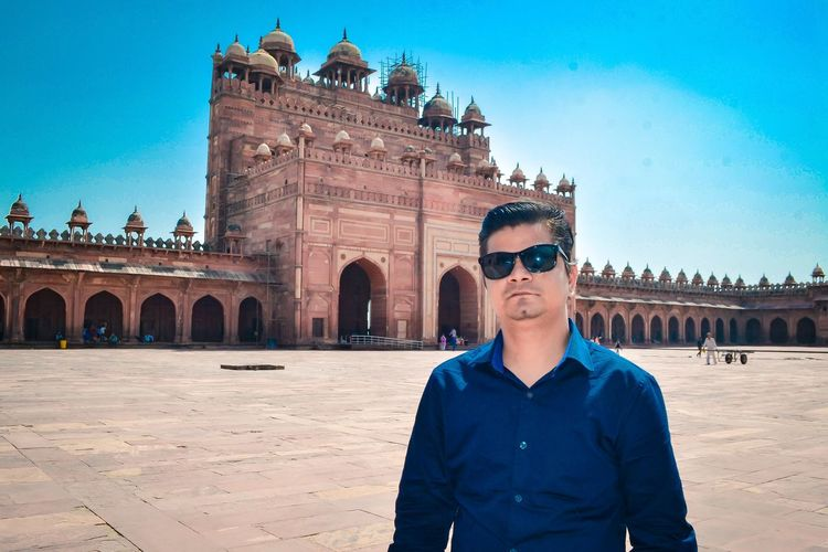 Portrait of man wearing sunglasses standing against fort