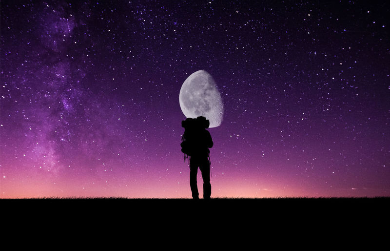 Silhouette hiker standing against moon with star field at night