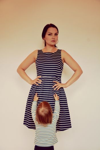 Rear View Of Baby With Arms Raised Standing By Mother Against Wall