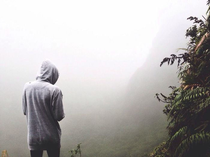 Rear View Of Person Wearing Hooded Shirt Against Mountain In Foggy Weather