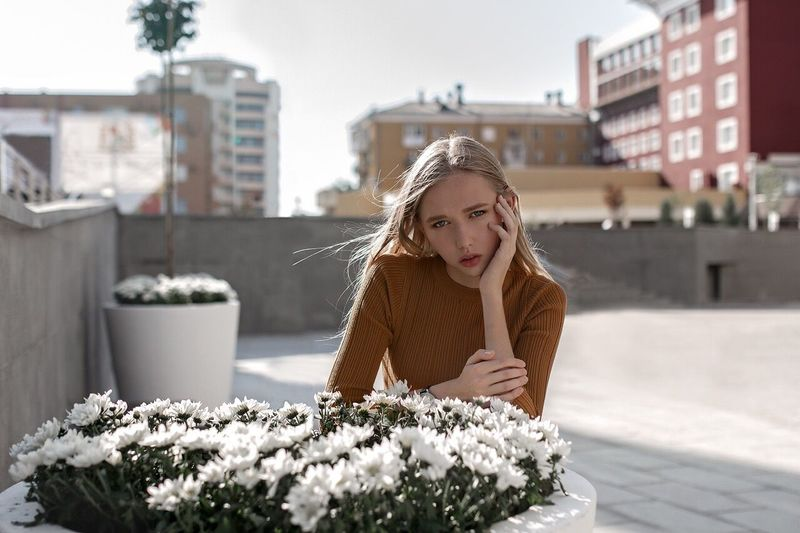 Young woman with flowers in city