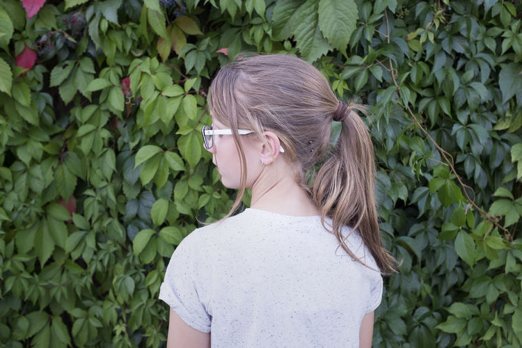 Rear view of girl standing by plants in park