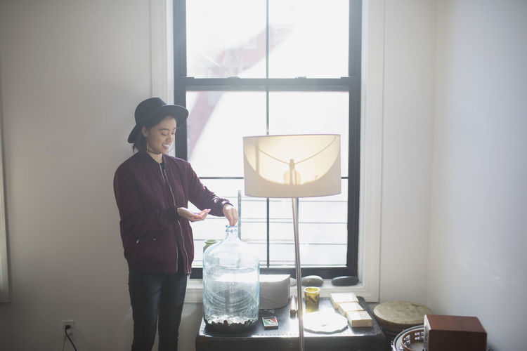 Man holding glass while standing by window at home