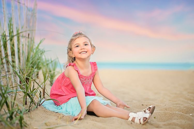 Portrait of happy girl sitting on sand at beach against sky