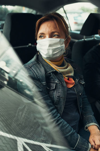 Woman sitting in a car wearing the face mask to avoid virus infection