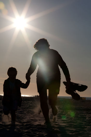 Silhouette of mother and daughter running at beach during sunset