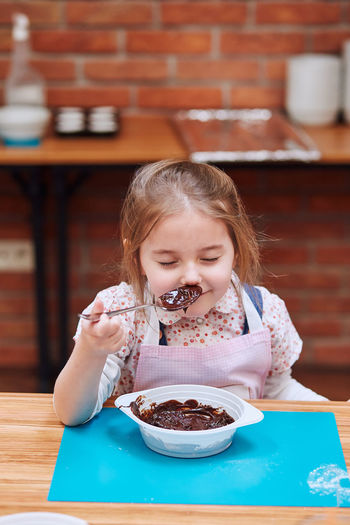 Girl smelling batter on table at home