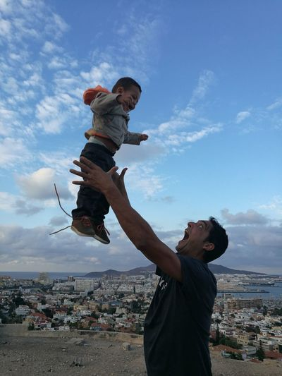 Father Catching Boy Against Sky