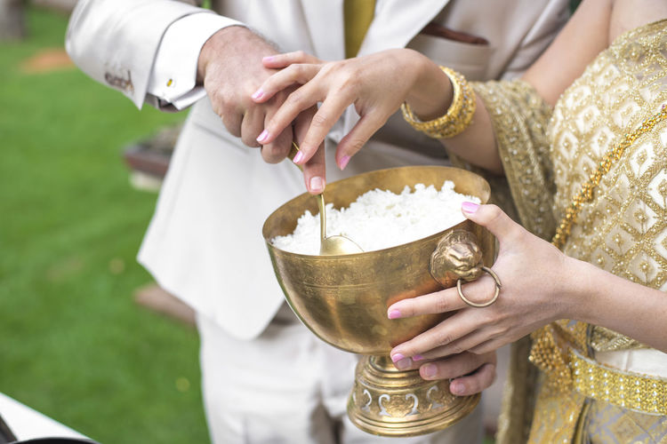 Midsection of couple holding rice in container during wedding ceremony