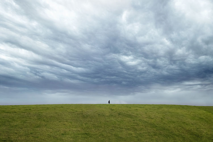 Person walking on hill against cloudy sky