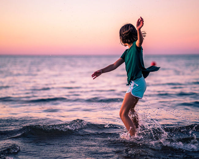 Full length of girl playing on beach during sunset