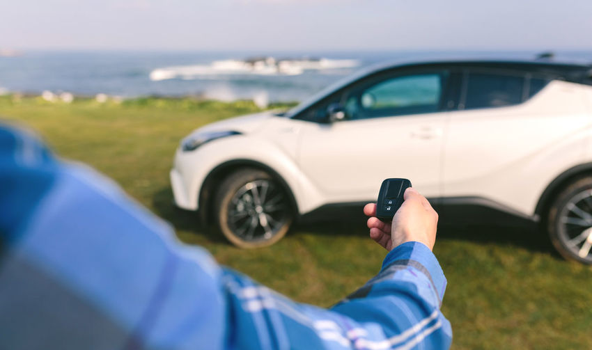 Cropped image of man holding car remote on field