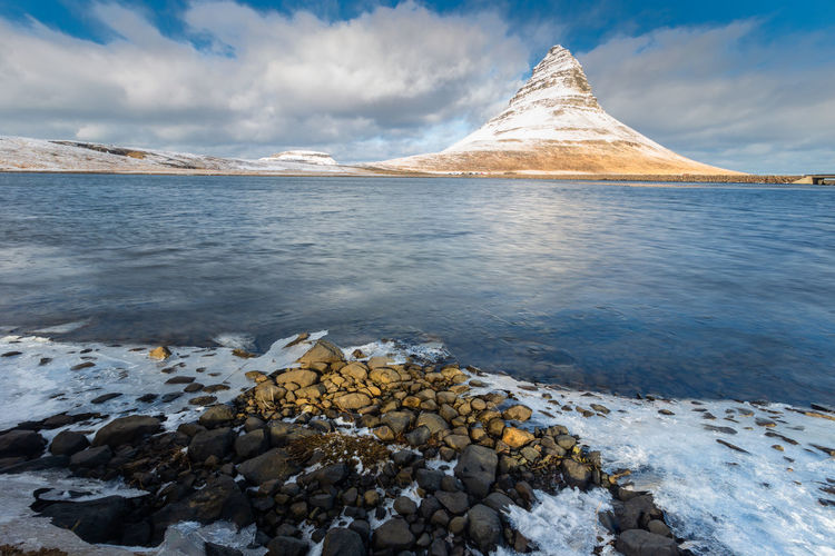 Kirkjufell mountain in winter season Iceland Iceland Kirkjufell Beauty In Nature Cloud - Sky Cold Temperature Day Idyllic Mountain Mountain Peak Nature No People Non-urban Scene Outdoors Rock Rock - Object Scenics - Nature Sky Snow Snowcapped Mountain Solid Tranquil Scene Tranquility Water Winter