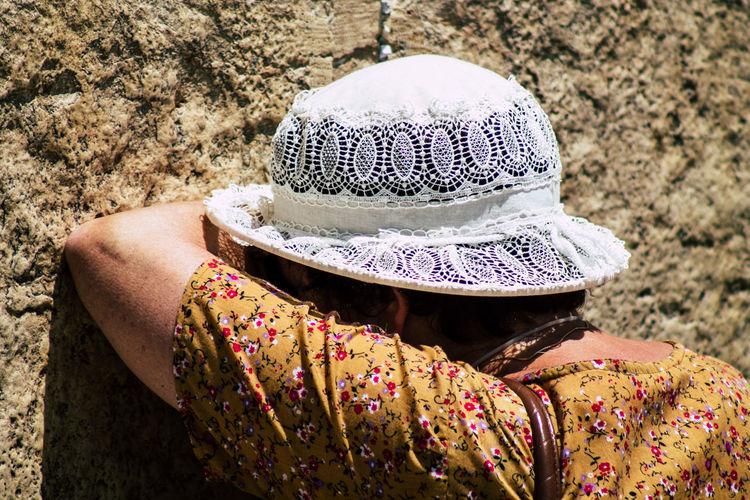 Rear view of woman wearing hat on rock