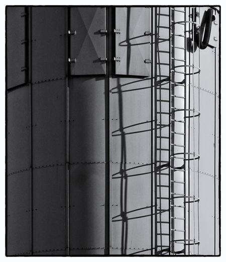 RUNGS AND RINGS: The side of a gas-holder. Bognor Regis, West Sussex, United Kingdom. Gas-holder Rungs Hoops Safety Shadows Monochrome Architecture Building Building Exterior Built Structure Day Development Industry Ladder Low Angle View Metal Nature No People Outdoors Sky Wall - Building Feature Working