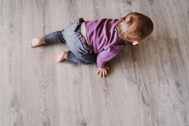 High angle view of baby lying on hardwood floor