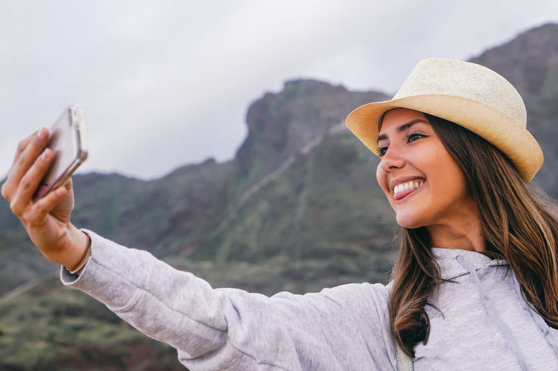Happy young woman sticking out tongue while taking selfie against mountains